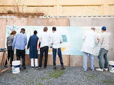 Los pintores realizando el Homenaje a Majo Okner
